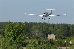 My Mom shot this photo of me landing at Holland Landing Airpark (CNA4). The 1960ft paved runway is great short-field practice. The plane is a Diamond Katana, belonging to National Flyers. June 2006 by Brigitte Vorkoetter.