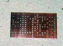 A clean, drilled, and deburred copper-clad board.