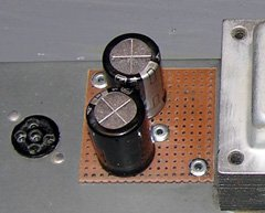 The new capacitors were neatly mounted on a piece of perfboard riveted to the amplifier chassis.