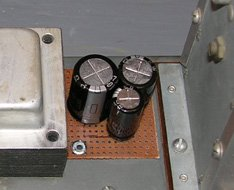 Three of the four replacement capacitors are on top of the chassis and the fourth is underneath.