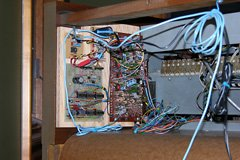 Plywood mounting board with circuitry installed on the right hand wall of the organ, with wires leading to the front.
