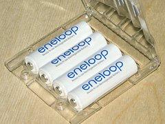 Four low-self-discharge Sanyo Eneloop AA batteries in their reusable storage pack.