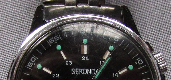 "A close-up of the upper half of the watch shows the deep scratches at 12 o'clock, and some more over the ""Sekonda"" label."