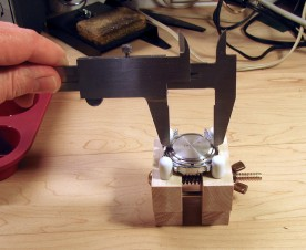 With the watch secured in a case holder, an inexpensive steel caliper makes a workable case back opening tool.