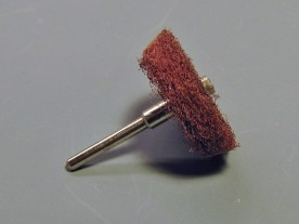 Brushing wheel cut from a Scotchbrite pad.