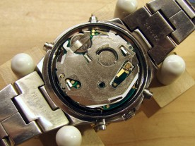 The movement reinstalled in the watch, with clear plastic insulating label.