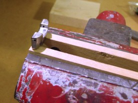 End link clamped in a hardwood-jawed vice for filing.