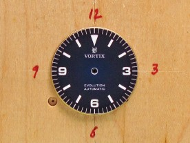 The dial holding block, precisely marked for artwork alignment.