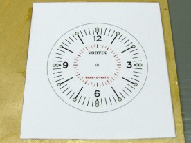 The printed dial artwork, epoxied to 1/16″ (1.6mm) plywood.
