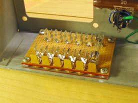 The fuse holder is fastened to the chassis with four 6-32 bolts and nuts.