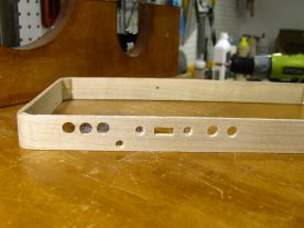 Completed holes along the top edge of the case, including countersunk screw holes.