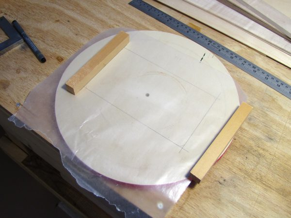 The jig was constructed on a piece of very flat plywood. The wax paper is to prevent the frame from sticking to the jig.