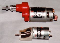 "Two typical single stage gearboxes. At the top is a Master Airscrew gearbox for Speed 600 size motors, which comes in 2.5:1, 3:1, and 3.5:1 ratios, and features ball bearings on the output shaft. At the bottom is a Modelair-Tech GB-50 for Speed 400 size motors. This is a simple, low-cost gearbox with a 2.14:1 ratio, metal gears, and an easily replaceable 1/8"" output shaft."