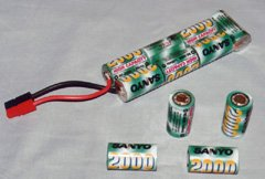 Battery and cells. At the top is a 7-cell battery (or pack) made up of seven Sanyo RC2000 cells. Four loose RC2000 cells are in the foreground. The battery was constructed by soldering two sticks of three cells end-to-end, and then soldering a seventh cell to the ends of the sticks using copper braid as a conductor. The whole pack is then enclosed in heat shrinkable plastic.