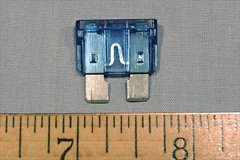 A typical automotive fuse. The short length of thin fuse wire is visible between the two spade connectors through the fuse body.