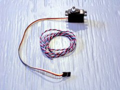 In a concession to mass production, modern servos like this Hitec HS-81 have flat parallel leads. Older servos used twisted leads like this vintage Ace R/C servo lead (center).
