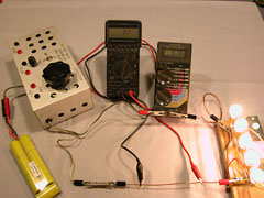 "Using one meter to measure current (the left one), the other meter's alligator clips are positioned on the shunt until it reads the same number of milliVolts as there are Amps flowing. This calibrates the shunt. The aluminum box is my bench-top ""speed control"", but here is just being used to connect the battery to the circuit."