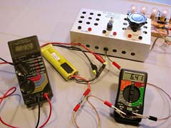 "Using the left hand meter to measure the voltage difference across a connection (7.2mV), and the right hand meter to measure current (6.41A), we can compute the resistance of the connection to be 1.1 milliOhms. (0.0011 Ohms). Pins are used to tap into the wire on either side of the connection. The current is from the 7xCP2400SCR battery powering five paralleled automotive lamps (top right) through my bench top ""speed control"" (a large variable resistor)."