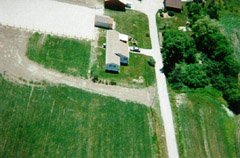 Here's a view of the mobile home and shed looking south, from about 500ft. You can see the end of the barn at the top of the photo. I'm visible at the left side, half way down the photo. The large whitish area is our riding/driving ring.